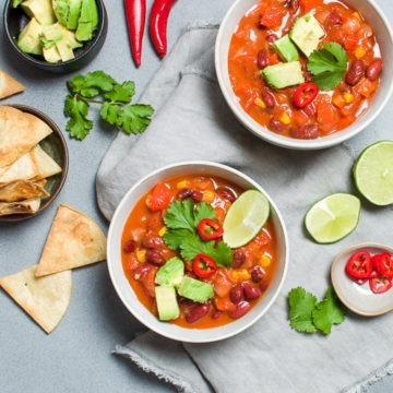 Two bowls of mexican bean soup with chillies & herbs