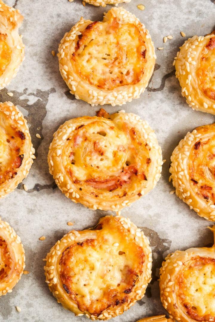 close up of ham and cheese pinwheels on baking tray