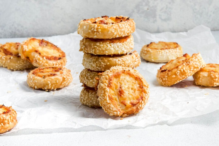 Stack of 5 puff pastry pinwheels with another pinwheel on its side to show swirls of ham and cheese