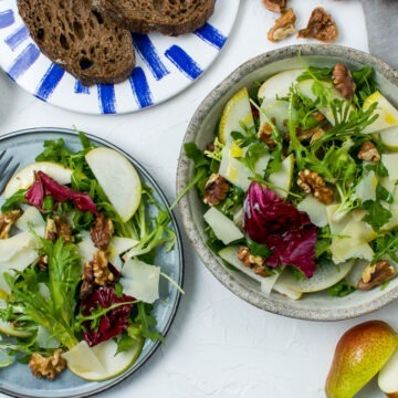 two plates of pear walnut salad with dark rye bread just visible in top of image