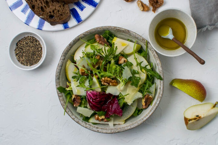 one shallow bowl of walnut and pear salad with leaves and parmesan with extra lemon dressing to the right and quartered pear to the bottom of the image