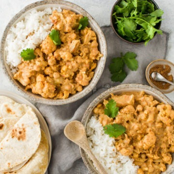 two bowls of coconut cauliflower chickpea curry with rice, with chapatis and fresh coriander and a small bowl of garam masala to sprinkle over the curry