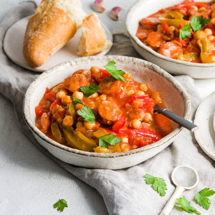 Spanish chickpea and chorizo stew sprinkled with parsley with fresh bread in the background