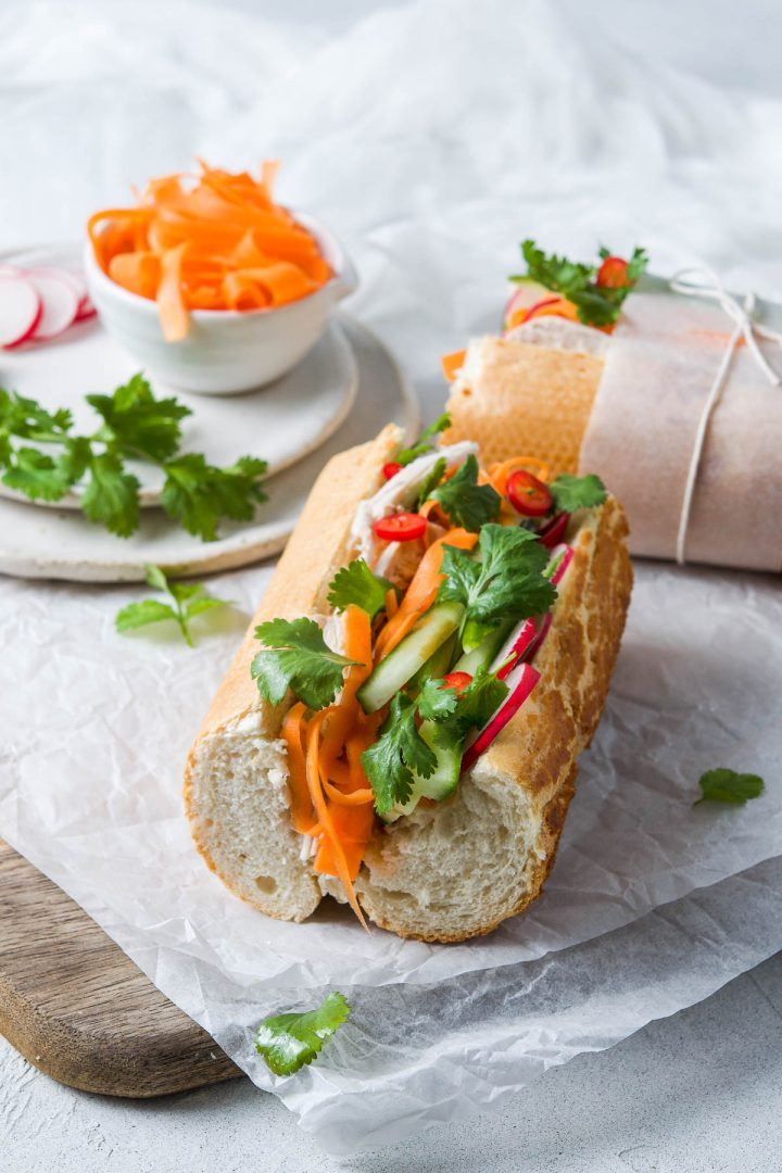 quarter of baguette filled with turkey, pickled carrot, radish, cucumber and coriander. Another quarter of baguette in the background, side to the camera, with baking paper tied with string around it