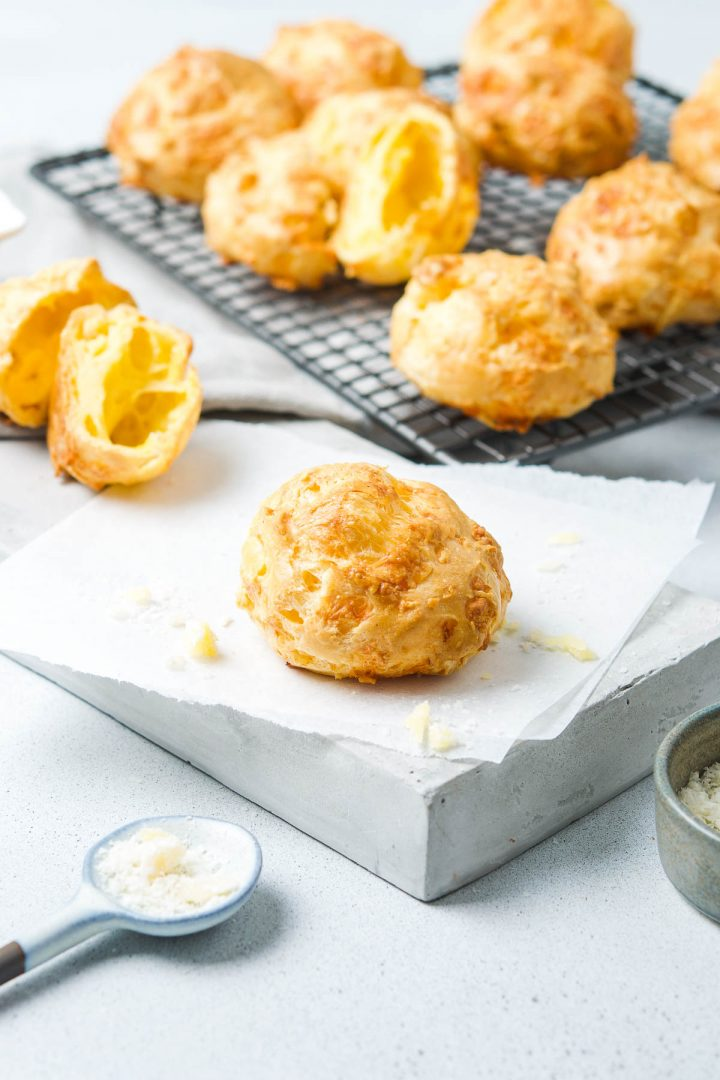 one cheese gougere in the foreground, the other cheese puffs on cooling rack in the background with one cut on the left to show the soft airy texture