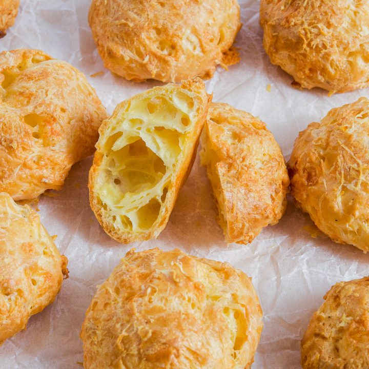 close up of cheese gougeres with one cut open to show the light and airy centre