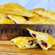 turkey turnovers with cranberry and cheese, one cut in half to show the ingredients