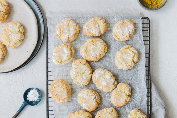 Baked Ricciarelli soft Italian cookies on baking paper and rack, with a small bowl of orange zest top right hand corner