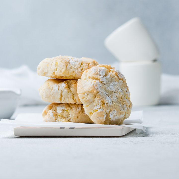 stack of three ricciarelli biscuits with another biscuit leaning to the right to show the cracked top