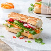 long side view of baguette filled with leftover turkey, radishes, carrot strips, fresh coriander and red chilli, with a white bowl of pickled carrot in the background together with another banh mi baguette