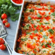 cheesy baked turkey enchiladas in baking dish topped with peppers and cilantro