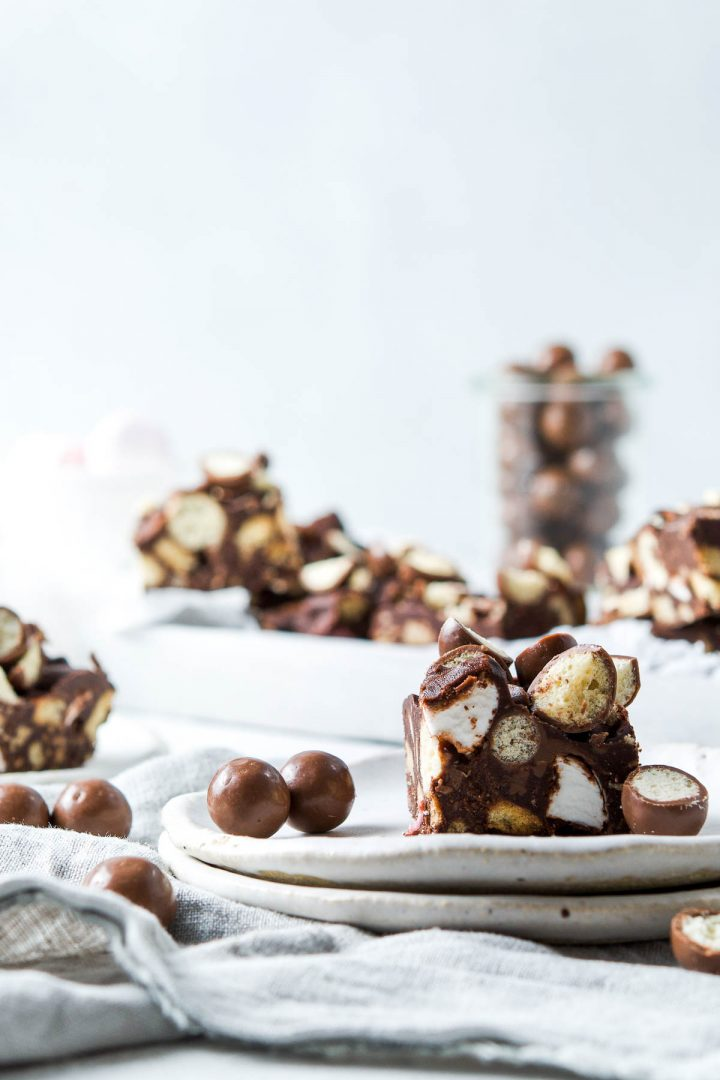 A slice of Maltesers rocky road on two plates, with Maltesers to the left. More of the traybake is in the background, together with a glass jar of maltesers