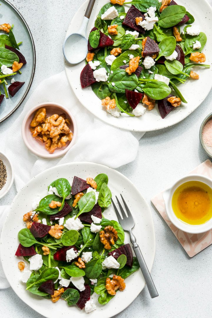 two white plates of beetroot and feta salad, with a blue plate just visible. Extra sweet and spicy walnuts and orange dressing to serve