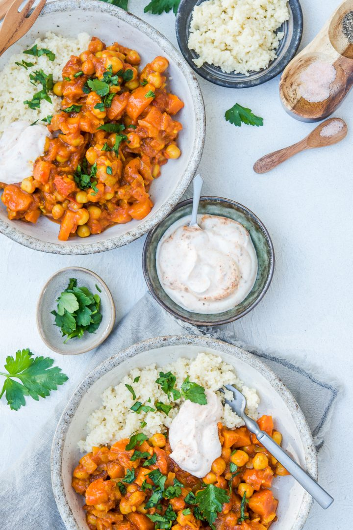 overhead shot of two bowls of chickpea tagine with couscous and harissa yogurt, extra yogurt in a bowl between them