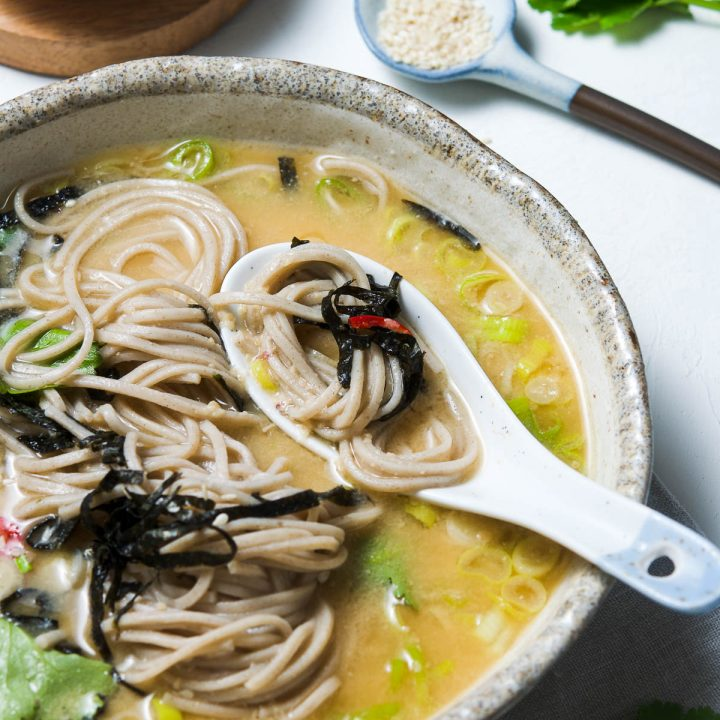 a close up of miso noodle soup being eaten with a spoon