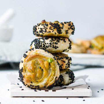 stack of 4 samosa pinwheels with nigella seeds on the outside. Another pinwheel is on its side to show the pinwheel pattern and filling