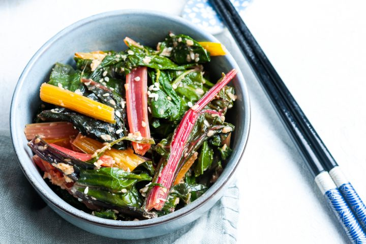 blue bowl of silverbeet with miso sesame dressing sprinkled with extra sesame seeds, a pair of chopsticks to the right