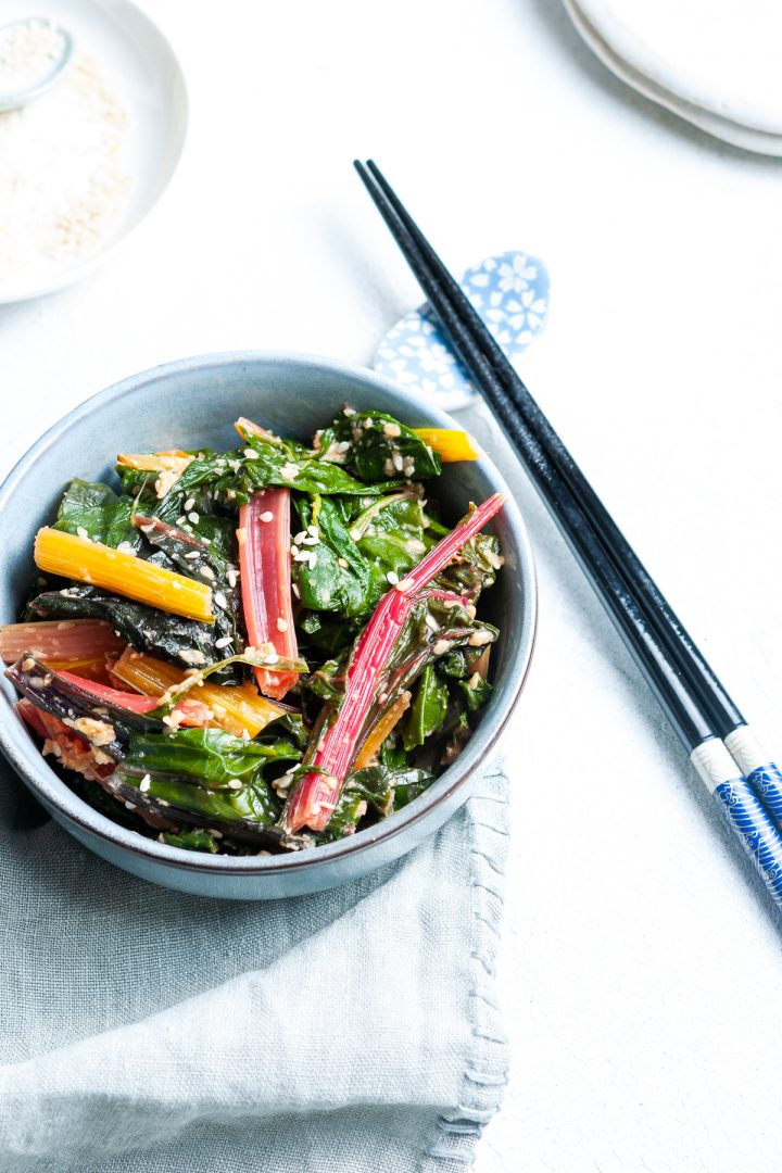 overhead of rainbow chard/silverbeet with sesame miso dressing, chopsticks to the right and extra sesame seeds to serve