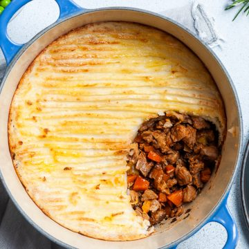 leftover lamb shepherds pie in baking dish with a section of potato taken off to show the juicy lamb layer underneath