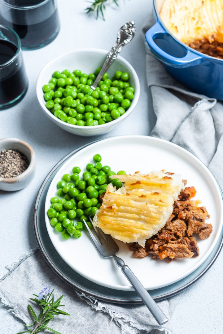 Serving of leftover lamb shepherds pie on a plate with peas ready to eat and a bowl of peas and a bowl of pepper next to it.