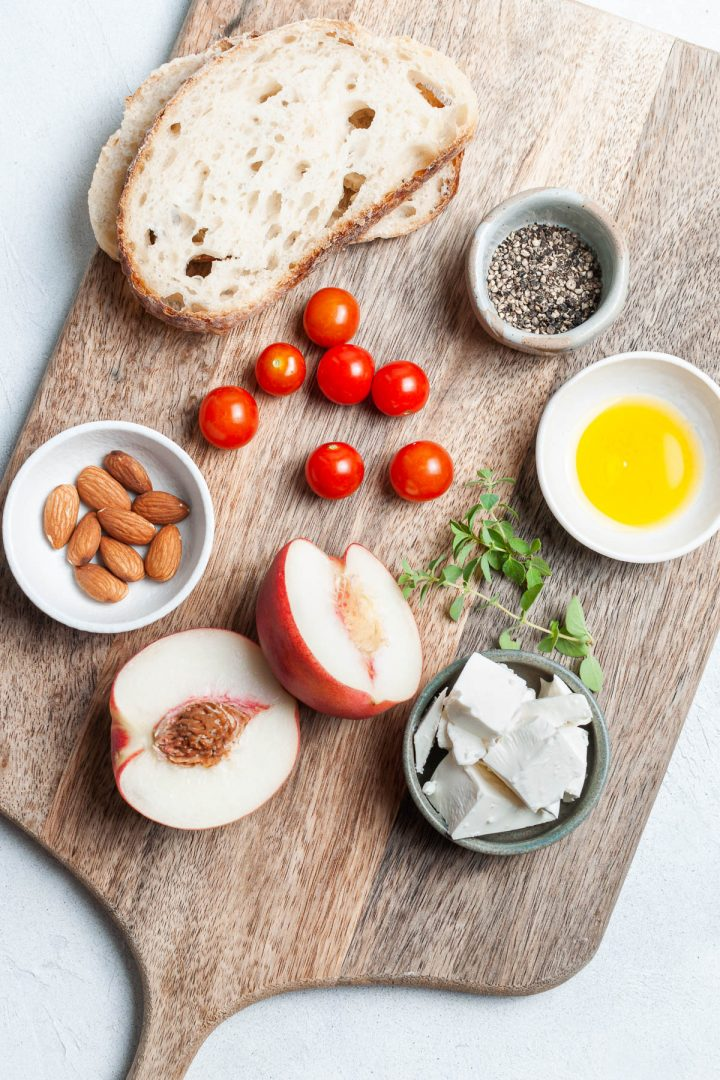 Ingredients for peach toast on wooden board: bread, peaches, feta, almonds, tomatoes, fresh oregano, olive oil and black pepper