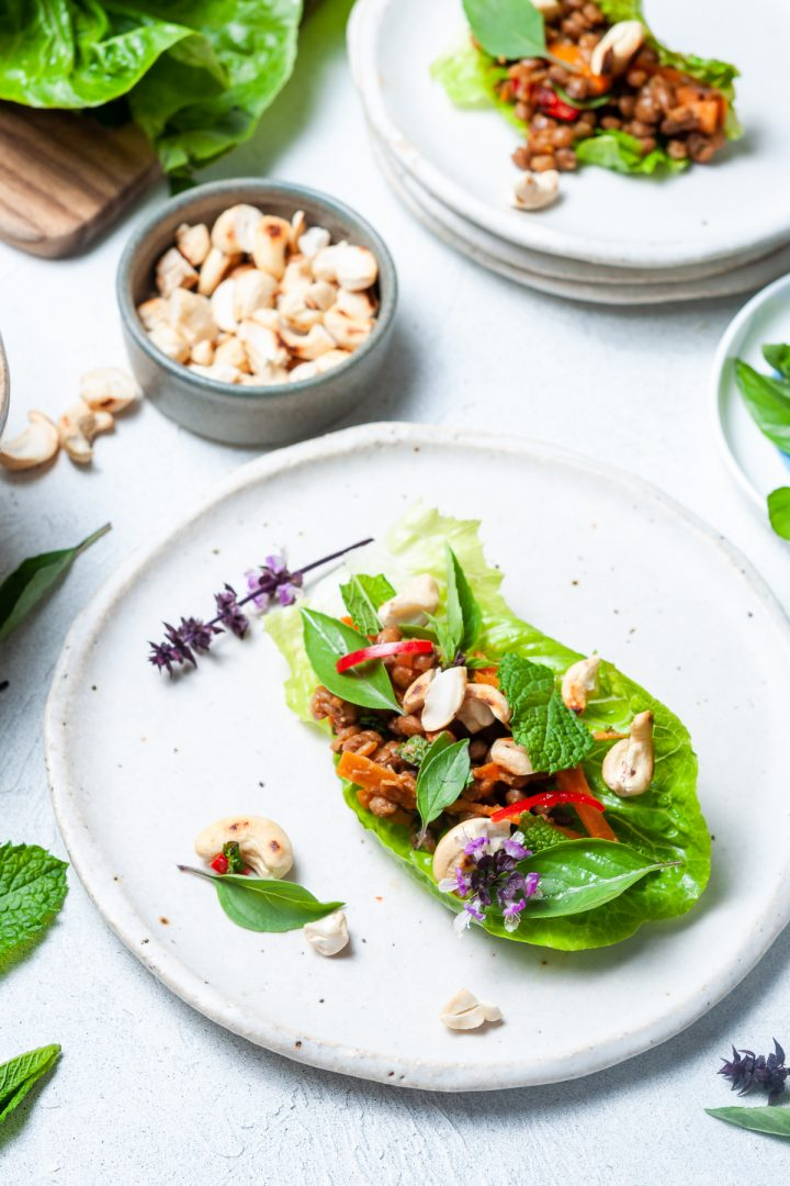 A lettuce wrap on a plate with bowl of nuts and other ingredients around, to show you can make them at the table