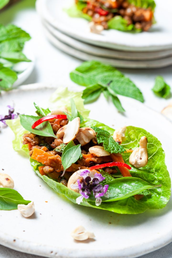 Close up of lettuce wraps so show the lentil, carrot, cashews and fresh herb filling