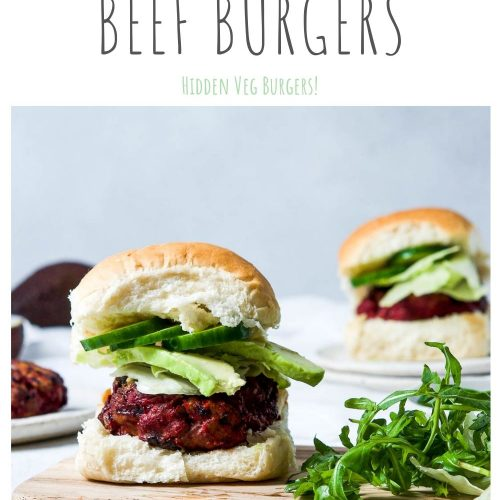 pin for beetroot beef burgers with hidden veg with one burger in a bun with avocado next to a handful of rocket (arugula)