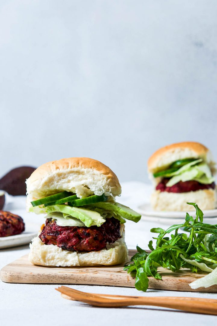 beetroot burger in a bread bun layered with avocado and cucumber, next to a handful of rocket