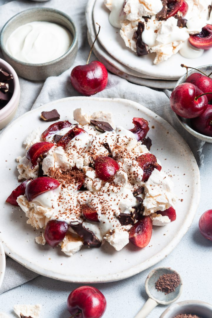 a plate of black forest eton mess with another plate just visible behind. Fresh cherries are dotted around the plates and bowls of cinnamon yogurt and chocolate almond crunch are just visible.