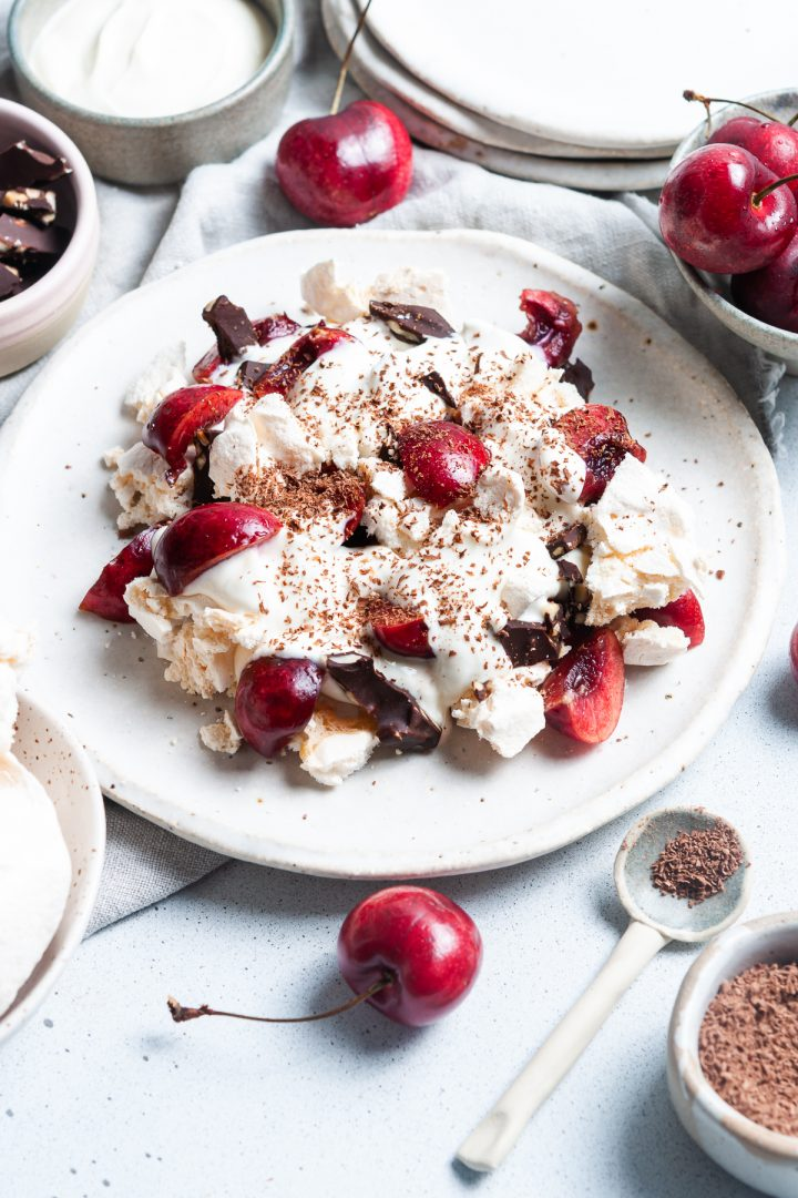 plate of black forest eton mess with fresh cherries topped with grated dark chocolate, with a bowl of grated chocolate and spoon to the front