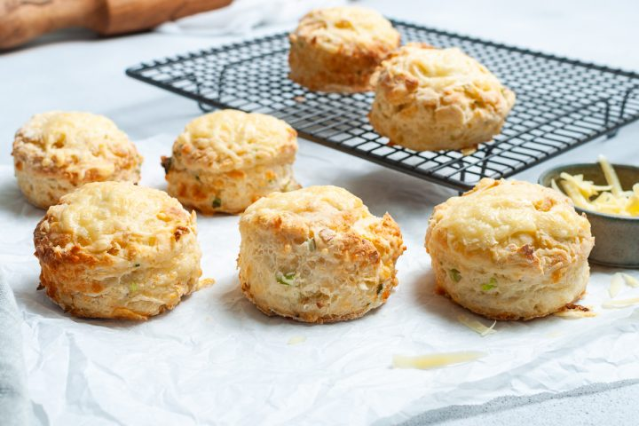 freshly baked cheese and onion scones, some cooling on a wire rack, others on baking paper