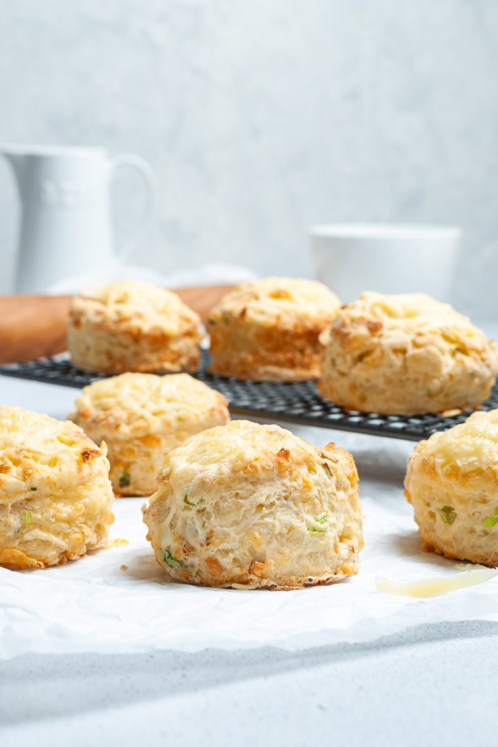 side view of cheese and onion scones to show they have risen, rolling pins and jugs just seen in background