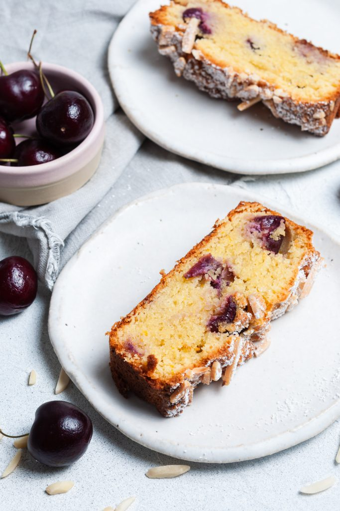 two slices of cherry bakewell cake on plates to show the light texture and colourful cherries