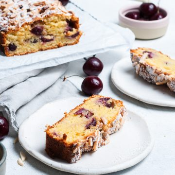 a slice of cherry bakewell cake on a white plate, with the rest of the loaf cake in the background