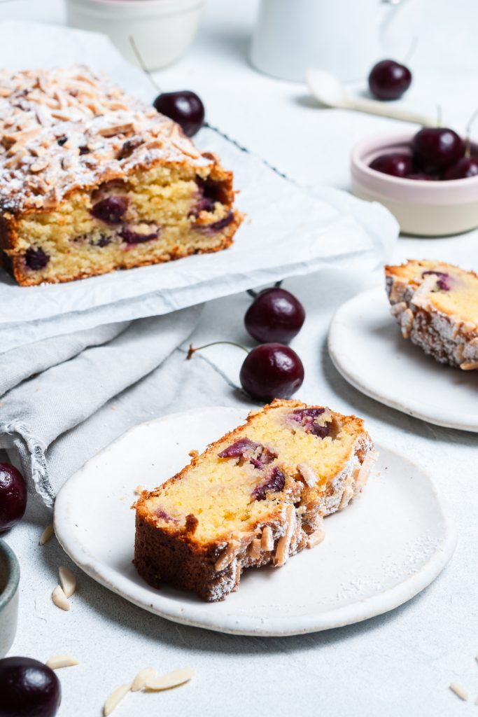 slice of bakewell cake with the finished cherry bakewell cake in the background, fresh cherries scattered around