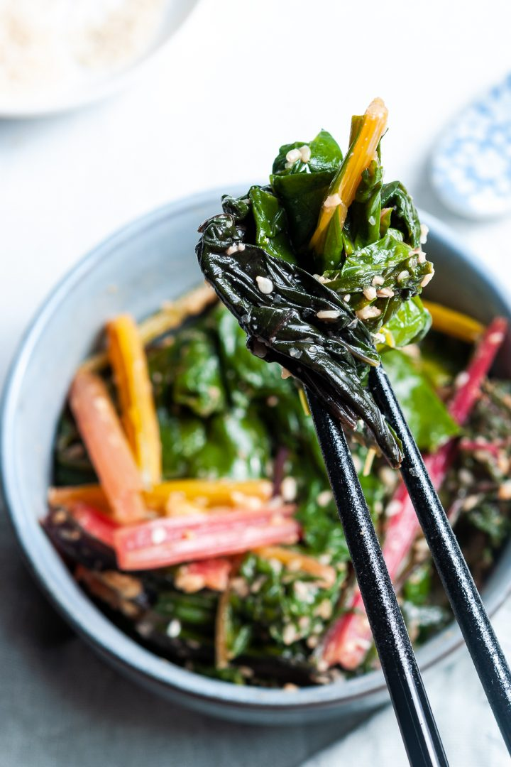 close up of silverbeet in chopsticks about to be eaten, showing the light sesame dressing