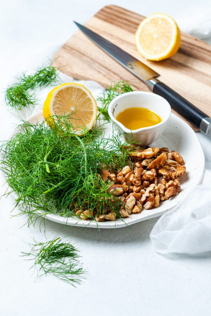 ingredients for dill pesto on white plate: fresh dill, walnuts, fresh lemon and olive oil
