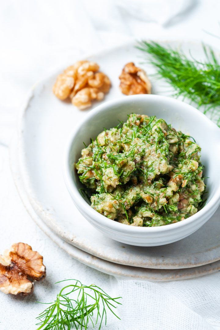 alngled image of walnut dill pesto in white dish with extra fresh dill and walnuts around it