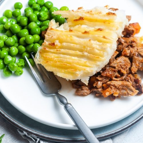 leftover lamb shepherds pie pin showing a serving of shepherds pie and peas