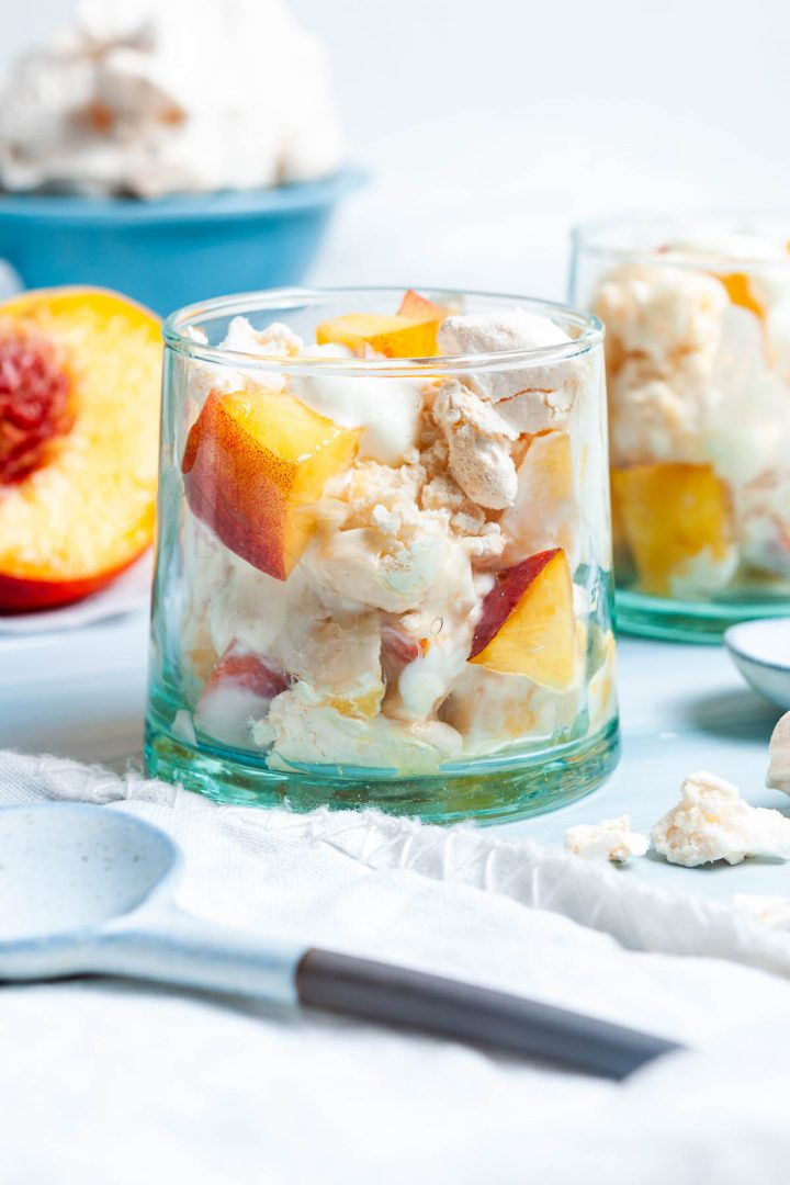 side view of glass filled with eton mess to show the ingredients: meringues, peaches and yogurt