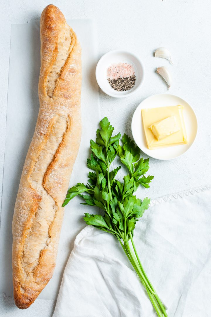 Air fryer ingredients laid out individually: fresh ciabatta baguette, small bunch of fresh parsley, 2 cloves of garlic, butter, salt and black pepper.