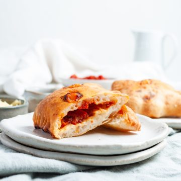 square image showing a cut pizza roll that has been cooked in the air fryer to show the fluffy dough and cheese and tomato pizza centre