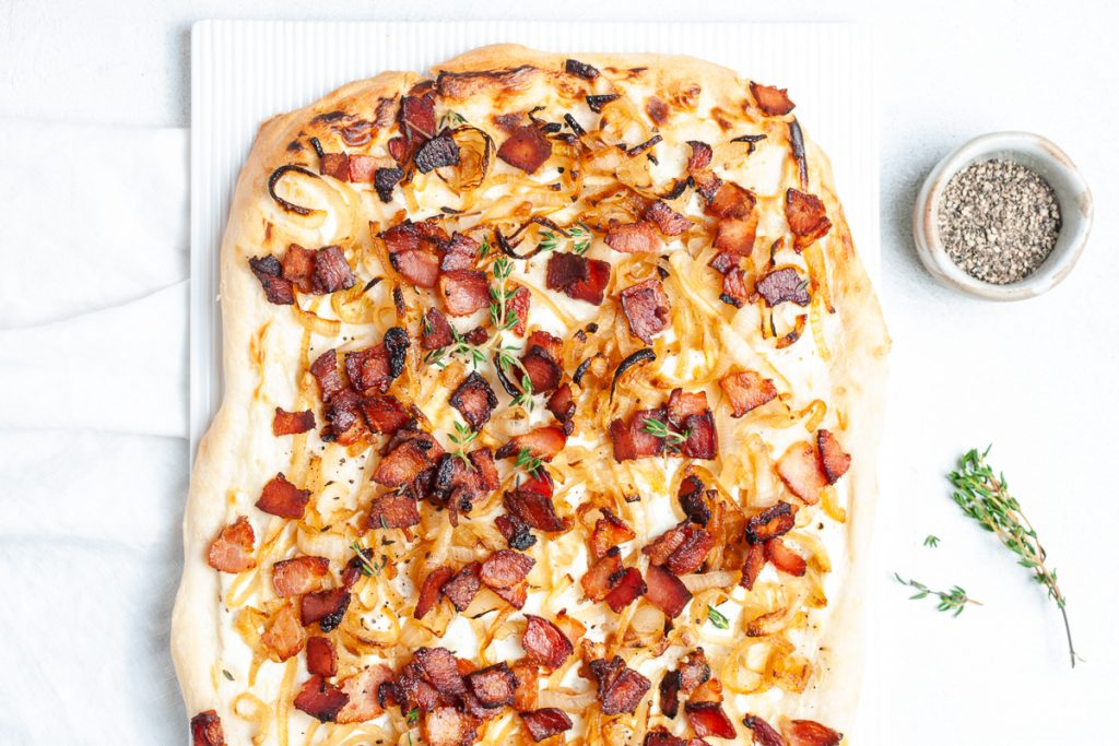 German pizza with bacon and onions on white background, fresh thyme sprinkled over it