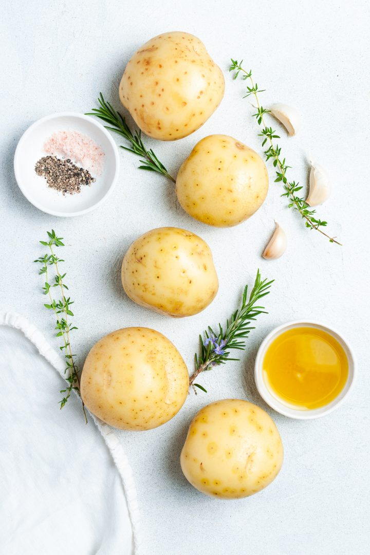 ingredients needed to make parmentier potatoes: potatoes, sprigs of fresh rosemary and thyme, olive oil, salt and black pepper