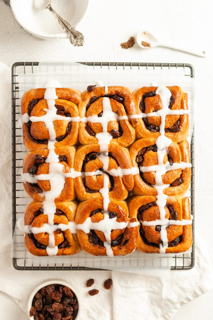 overhead shot of hot cross bun scrolls which have just been iced