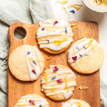 close up of lemon shortbread cookies on wooden board, decorated with lemon icing and edible flowers, ready to serve