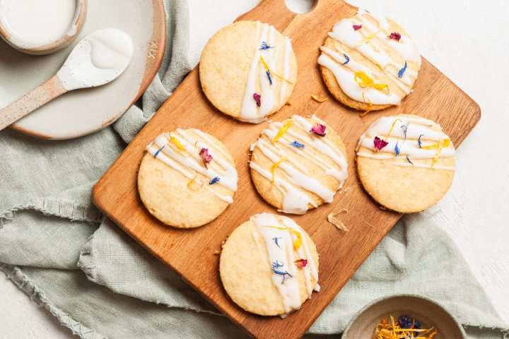 6 round lemon shortbread cookies on a wooden board, drizzled with lemon icing, extra icing and the spoon to the left of the image
