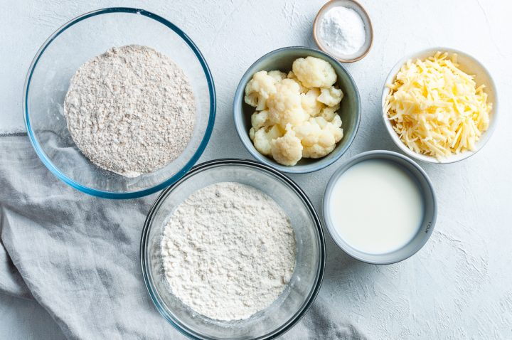 ingredients for cauliflower cheese scones laid out in individual bowls: wholemeal flour, plain flour, milk, grated cheese, baking powder and cooked cauliflower