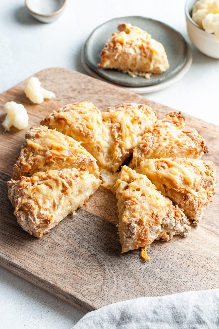 Angled shot of cauliflower scones on wooden board to show the melted cheese top and cooked centres, one scone on a plate ready to eat